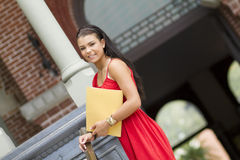 Happy female Student at entryway. A smiling female student holding railing outside of campus Royalty Free Stock Photos