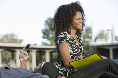 Happy Female Student With Friend Using Cell Phone Stock Photography