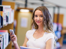 Happy female student holding books at the library Royalty Free Stock Image
