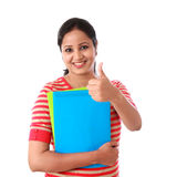 Happy female student holding text book and making thumb up gestu. Re against white Stock Photo