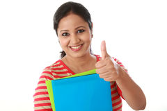 Happy female student holding text book and making thumb up. Gesture Stock Photo