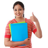 Happy female student holding text book and making thumb up Stock Photography