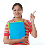 Happy female student holding text books Stock Photo