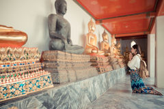 Happy female student kneeling in front of buddha Royalty Free Stock Image