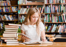 Happy female student with laptop in library.  Royalty Free Stock Images