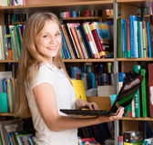 Happy female student with laptop in library Stock Image