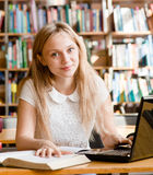 Happy female student with laptop in library.  Stock Image