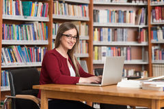 Happy Female Student With Laptop In Library. In The Library - Beautiful Female Student With Laptop And Books Working In A High School - University Library Royalty Free Stock Photos