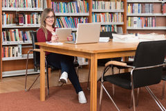 Happy Female Student With Laptop In Library. In The Library - Beautiful Female Student With Laptop And Books Working In A High School - University Library Stock Photo