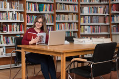 Happy Female Student With Laptop In Library. In The Library - Beautiful Female Student With Laptop And Books Working In A High School - University Library Royalty Free Stock Image