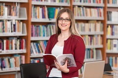 Happy Female Student With Laptop In Library. In The Library - Beautiful Female Student With Laptop And Books Working In A High School - University Library Royalty Free Stock Images