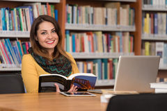 Happy Female Student With Laptop In Library. In The Library - Beautiful Female Student With Laptop And Books Working In A High School - University Library Stock Photos