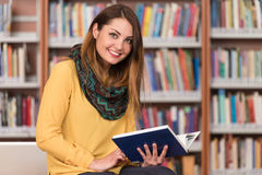 Happy Female Student With Laptop In Library. In The Library - Beautiful Female Student With Laptop And Books Working In A High School - University Library Stock Images