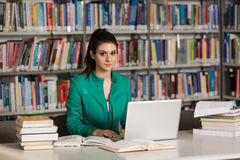 Happy Female Student With Laptop In Library Stock Photo