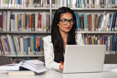 Happy Female Student With Laptop In Library Royalty Free Stock Photography