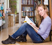 Happy female student in library looking at camera Royalty Free Stock Photo