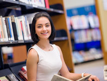 Happy female student at the library. Happy young female student sudying at the library Royalty Free Stock Photos