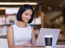 Happy female student at the library. Happy young female student sudying at the library Royalty Free Stock Image