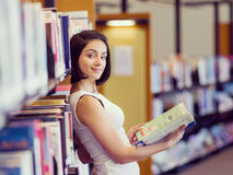 Happy female student at the library. Happy young female student sudying at the library Royalty Free Stock Images