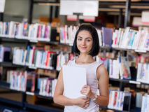 Happy female student at the library. Happy young female student sudying at the library Royalty Free Stock Photo