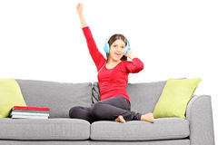 Happy female student listening music seated on a couch Stock Photos