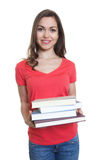 Happy female student with long dark hair looking and books Stock Photo