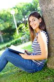 Happy female student in park in summer smiling Royalty Free Stock Photo