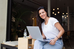 Happy female student posing for the camera while work on net-book and resting after lectures in coffee shop, Stock Image