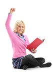 A happy female student reading a book stock images