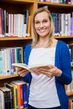 Happy female student reading a book in the library Stock Images