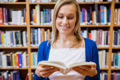 Happy female student reading a book in the library. At the university Stock Photos