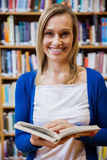 Happy female student reading a book in the library Royalty Free Stock Photo