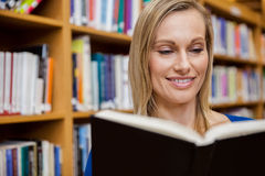 Happy female student reading a book in the library Royalty Free Stock Photography