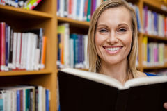 Happy female student reading a book in the library. At the university Royalty Free Stock Photo