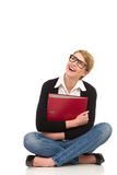 Happy female student sitting with crossed legs. Royalty Free Stock Image