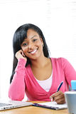 Happy female student studying. Portrait of smiling young black female student studying at desk Royalty Free Stock Photos