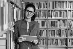 Happy Female Student With Tablet In Library. In The Library - Pretty Female Student With Tablet And Books Working In A High School - University Library - Shallow Stock Image