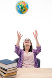 Happy female student throwing globe into air Stock Photo
