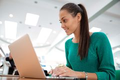Happy female student using laptop in university Royalty Free Stock Photos