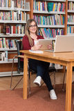 Happy Female Student Working With Laptop In Library. In The Library - Beautiful Female Student With Laptop And Books Working In A High School - University Royalty Free Stock Photo