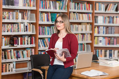 Happy Female Student Working With Laptop In Library. In The Library - Beautiful Female Student With Laptop And Books Working In A High School - University Royalty Free Stock Images