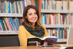 Happy Female Student Working With Laptop In Library. In The Library - Beautiful Female Student With Laptop And Books Working In A High School - University Stock Photo