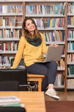 Happy Female Student Working With Laptop In Library. In The Library - Beautiful Female Student With Laptop And Books Working In A High School - University Royalty Free Stock Photography