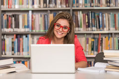 Happy Female Student Working With Laptop In Library Royalty Free Stock Photo
