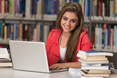 Happy Female Student Working With Laptop In Library Stock Photo