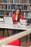 Happy Female Student Working With Laptop In Library Royalty Free Stock Images