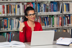 Happy Female Student Working With Laptop In Library Royalty Free Stock Photos