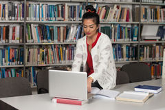 Happy Female Student Working With Laptop In Library Stock Image