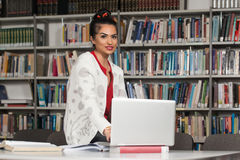 Happy Female Student Working With Laptop In Library Stock Photos