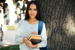 Happy female student writing notes in notepad Royalty Free Stock Photos